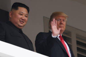 President Donald Trump (R) waves as he and North Korea's leader Kim Jong Un look on from a veranda during their historic U.S.-North Korea summit, at the Capella Hotel on Sentosa island in Singapore on June 12, 2018. Photo by Saul Loeb/AFP/Getty Images