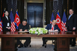 In this handout photograph provided by The Strait Times, North Korean leader Kim Jong-un with U.S. President Donald Trump sign a document. The contents of the document have not yet been released. Photo by Kevin Lim/The Strait Times/Handout/Getty Images