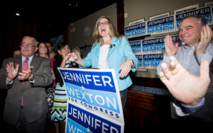 UNITED STATES - JUNE 12: Jennifer Wexton, center, speaks flanked by Rep. Gerry Connolly, D-Va., left, and Sen. Tim Kaine, D-Va., at her primary election night party at O'Faolin's Irish Pub in Sterling, Va., on Tuesday, June 12, 2018. Wexton won the primary to face incumbent Rep. Barbara Comstock, R-Va., in Virginia's 10th Congressional district. (Photo By Bill Clark/CQ Roll Call)