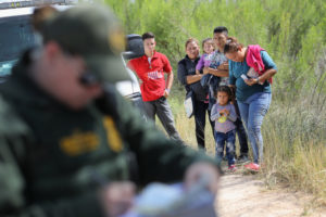 Central American asylum seekers wait as U.S. Border Patrol agents take groups of them into custody in June near McAllen, Texas. Photo by John Moore/Getty Images