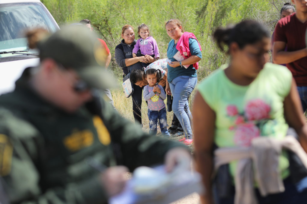 Central American asylum seekers wait as U.S. Border Patrol agents take them into custody on June 12, near McAllen, Texas. Photo by John Moore/Getty Images