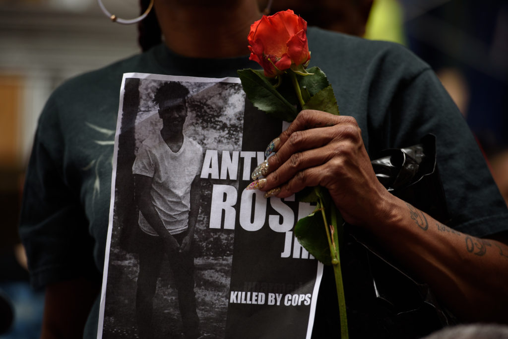 A woman holds a rose and a sign for Antwon Rose as she joins more than 200 people gathered for a rally to protest the fatal shooting of Rose at the Allegheny County Courthouse on June 21, 2018 in Pittsburgh, Pennsylvania. Photo by Justin Merriman/Getty Images