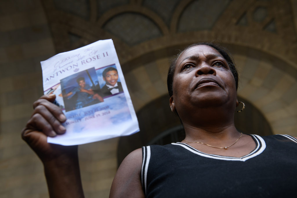 Carmen Ashley, the great aunt of Antwon Rose II, cries as she holds the memorial card from Rose's funeral during a protest calling for justice for the 17-year-old on June 26, 2018 in downtown Pittsburgh, Pennsylvania. Photo by Justin Merriman/Getty Images