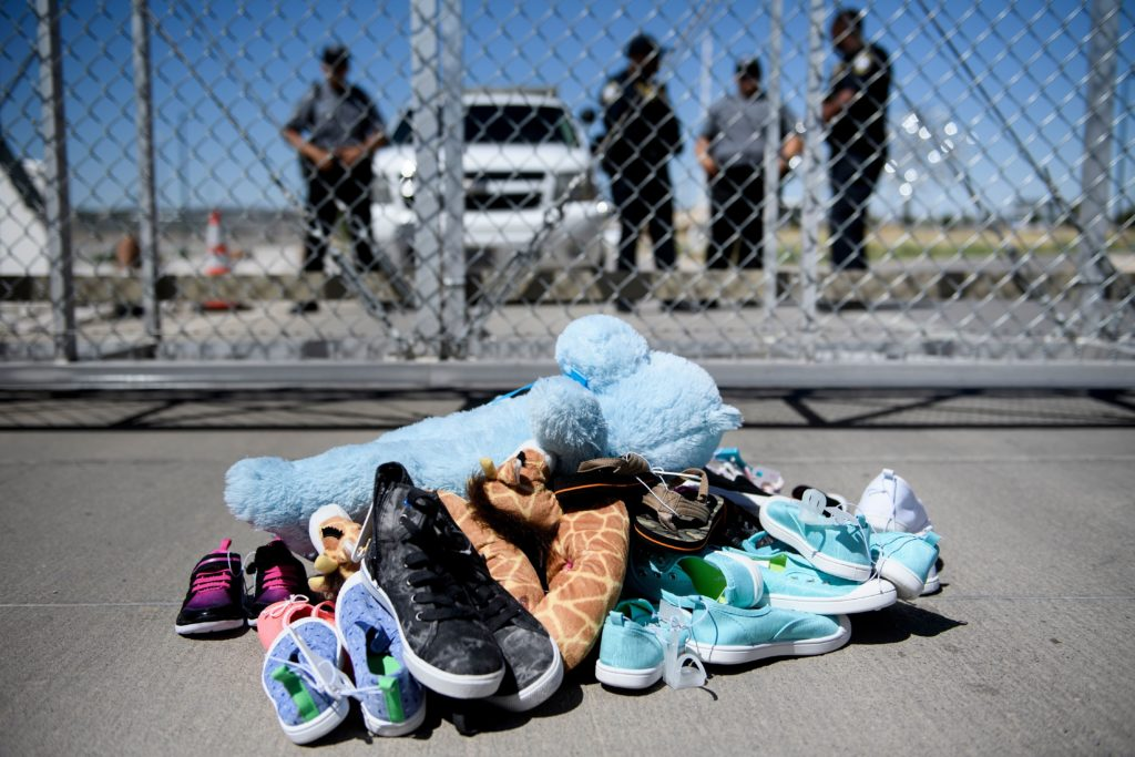 Security personnel stand before shoes and toys left at the Tornillo Port of Entry where minors crossing the border without proper papers have been housed after being separated from adults on June 21, 2018 in Tornillo, Texas. Photo by Brendan Smialowski/AFP/Getty Images