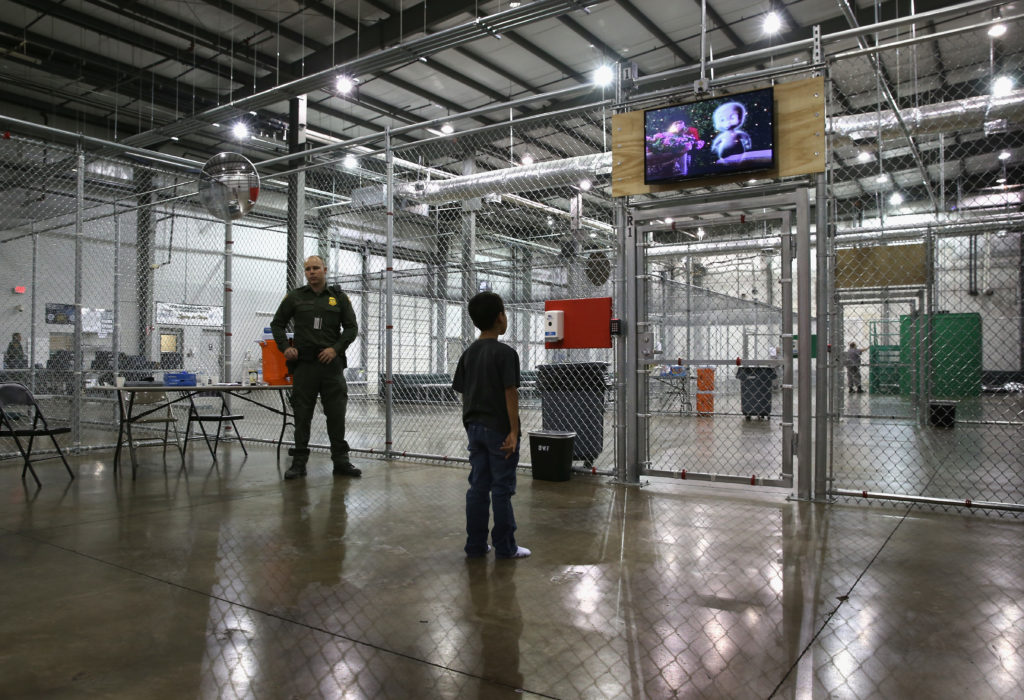 A boy from Honduras watches a movie at a detention facility run by the U.S. Border Patrol on Sept. 8, 2014 in McAllen, Texas. Photo by John Moore/Getty Images