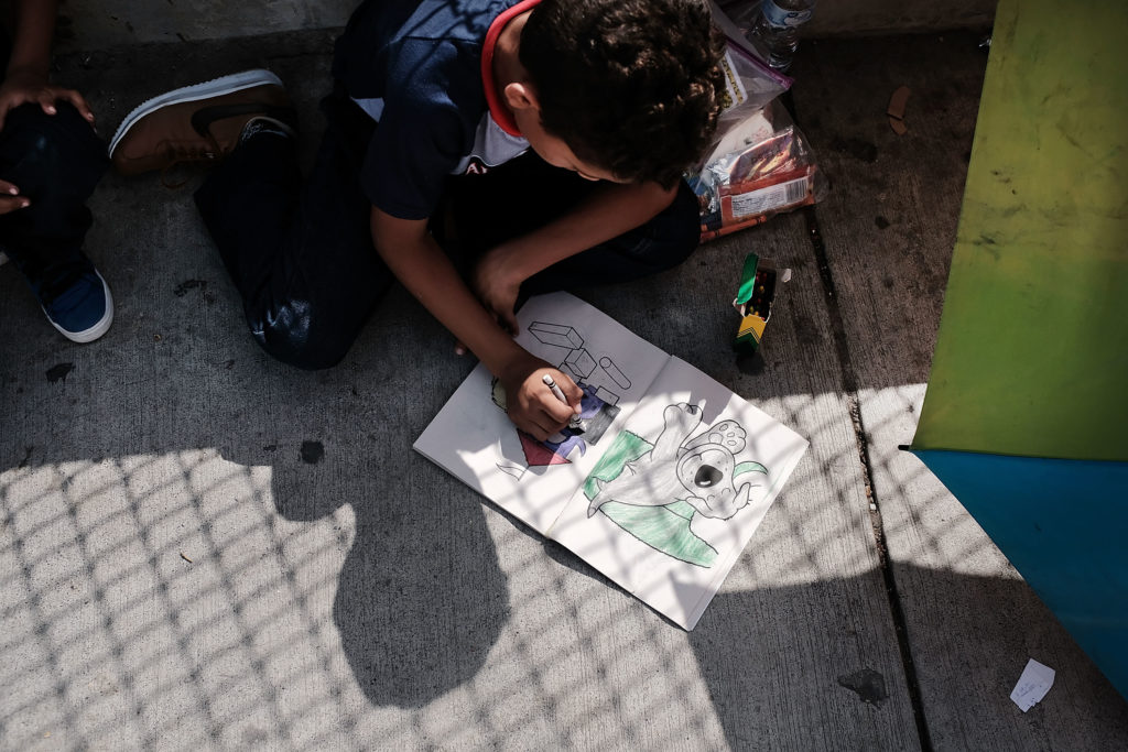A Honduran child works in a coloring book while waiting with his family along the border bridge after being denied entry from Mexico into the U.S. on June 25 in Brownsville, Texas. Photo by Spencer Platt/Getty Images