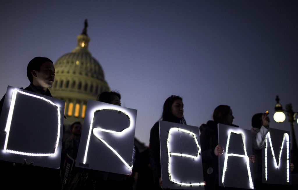 Demonstrators hold illuminated signs during a rally supporting the Deferred Action for Childhood Arrivals program (DACA), ...