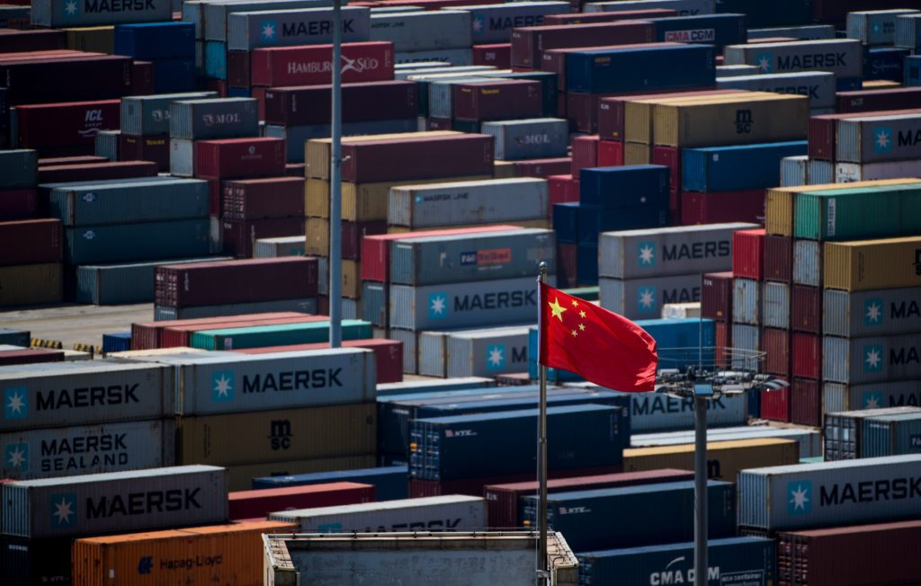 A Chinese flag is seen in front of containers at the Yangshan Deep-Water Port, an automated cargo wharf, in Shanghai. Phot...