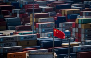 A Chinese flag is seen in front of containers at the Yangshan Deep-Water Port, an automated cargo wharf, in Shanghai. Photo by Johannes Eisele/AFP/Getty Images