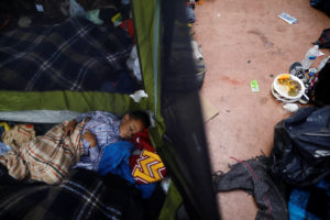 A child traveling with a caravan of migrants from Central America sleeps at a camp near the San Ysidro checkpoint, after U.S. border authorities allowed the first small group of women and children entry from Mexico overnight, in Tijuana, Mexico. Photo by Edgard Garrido/Reuters