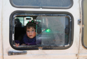 A child looks out of a window as Syrian refugees prepare to return to Syria from the Lebanese border town of Arsal, Lebanon. Photo by Mohamed Azakir/Reuters