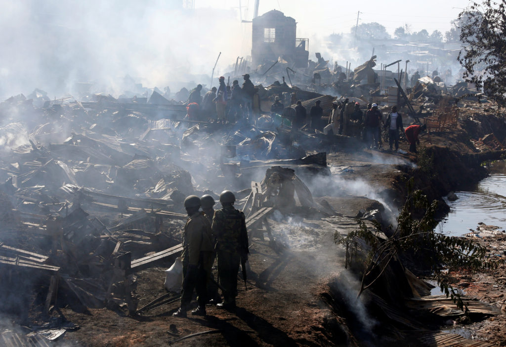 Traders and riot police are seen at the smouldering scene of fire that gutted down the timber dealership of the Gikomba market and nearby homes in central Nairobi, Kenya June 28, 2018. REUTERS/Thomas Mukoya