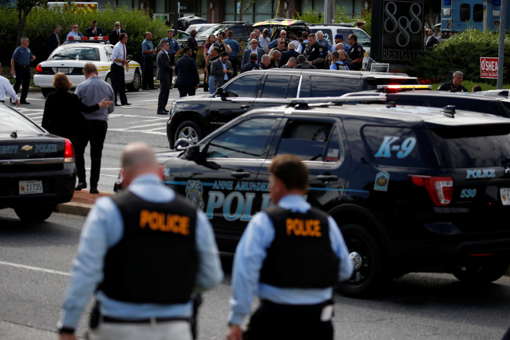 Law enforcement officials survey the scene after a gunman fired through a glass door at the Capital Gazette newspaper and sprayed the newsroom with gunfire, killing at least five people and injuring several others, in Annapolis, Maryland. Photo by Joshua Roberts/Reuters