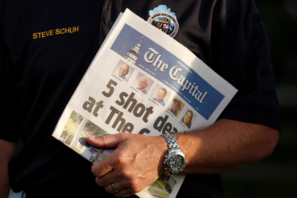 Steve Schuh, the County Executive of Anne Arundel County, Maryland, holds a copy of the Capital Gazette as he is interviewed the day after a gunman killed five people and injured two others at the newspaper's offices, in Annapolis, Maryland. Photo by Joshua Roberts/Reuters