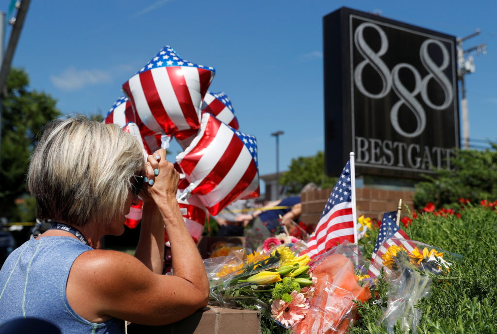 Kim Wither says a prayer at an impromptu memorial outside of the Capital Gazette, the day after a gunman killed five people inside the newspaper's building in Annapolis, Maryland. Photo by Leah Millis/Reuters