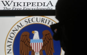A man is silhouetted near logos of the U.S. National Security Agency (NSA) and Wikipedia in this photo illustration taken in Sarajevo