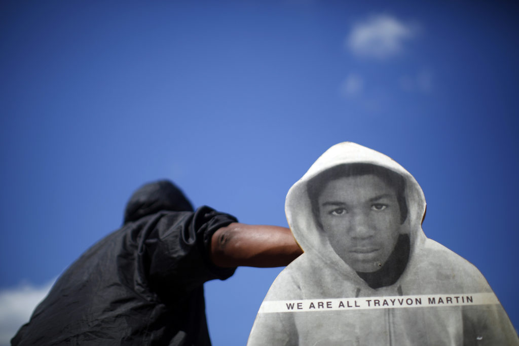 "A man holds up a cardboard cut out of Trayvon Martin at a rally in reaction to the acquittal of George Zimmerman in New York July 14, 2013. Thousands of protesters chanting ""No justice, no peace"" gathered in New York City on Sunday to protest the acquittal of George Zimmerman in the shooting death of unarmed black teenager Trayvon Martin, which prompted rallies across the country. REUTERS/Eric Thayer (UNITED STATES - Tags: CRIME LAW CIVIL UNREST POLITICS TPX IMAGES OF THE DAY) - GM1E97F0R5Y01"