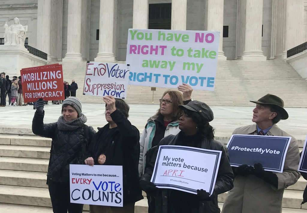 Activists rally outside the Supreme Court in January, ahead of arguments in a key voting rights case involving a challenge to the Ohio's policy of purging infrequent voters from voter registration rolls. Photo by Lawrence Hurley/Reuters