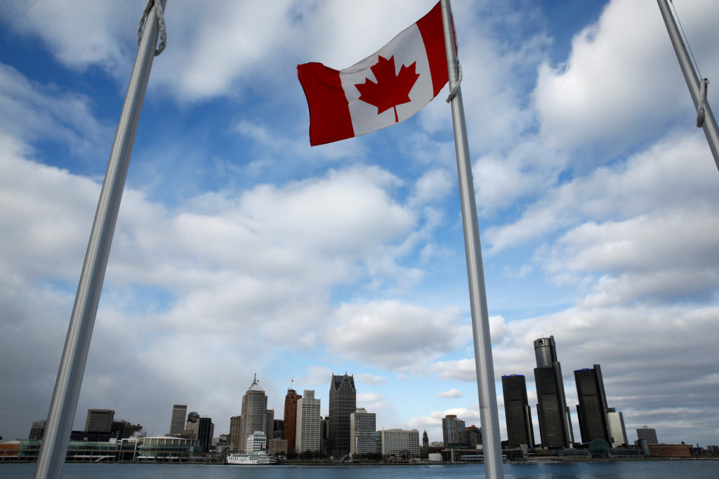 A Canadian flag flutters in front of the Detroit skyline, dominated by General Motors headquarters (R), is seen from Windsor, Onatario, Canada January 14, 2018.