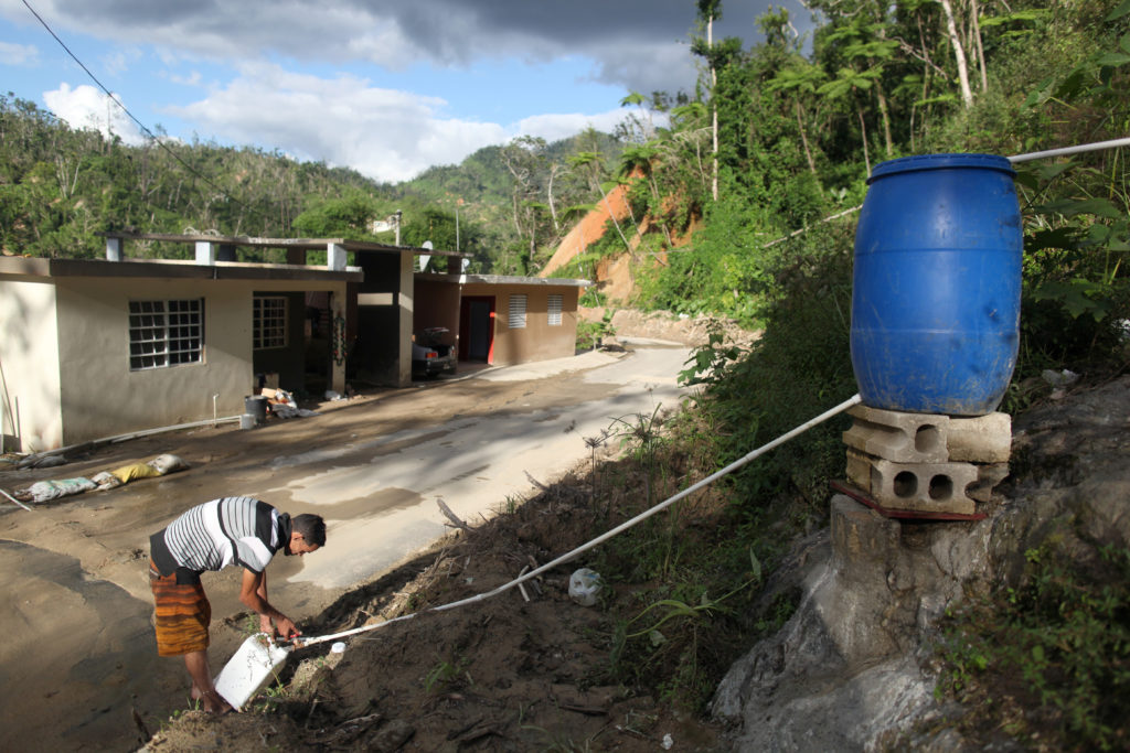 Juan Cosme fills a container with mountain spring water outside his home, after Hurricane Maria hit the island in September 2017, in Utuado, Puerto Rico February 1, 2018. Picture taken February 1, 2018. REUTERS/Alvin Baez