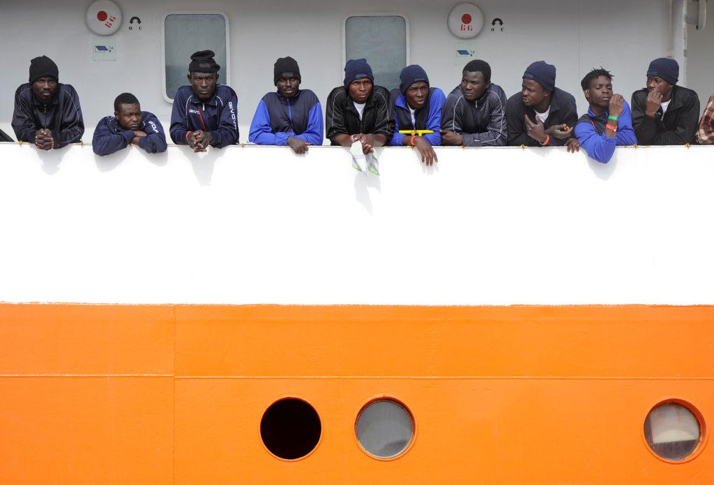 Migrants wait to disembark from Aquarius in the Sicilian harbor of Catania, Italy. Photo by Guglielmo Mangiapane/Reuters