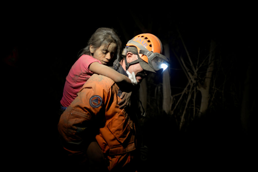 A rescue worker carries a child covered with ash after Fuego volcano erupted violently in El Rodeo, Guatemala. Photo by Fabricio Alonzo/Reuters