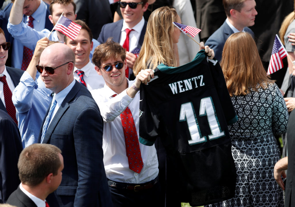 """A guest holds up the NFL jersey of Philadelphia Eagles quarterback Carson Wentz at U.S. President Donald Trump's """"celebration of America"""" event on the South Lawn of the White House in Washington, U.S., June 5, 2018. The event was arranged after Trump canceled the planned visit of the Super Bowl champion Philadelphia Eagles to the White House. REUTERS/Kevin Lamarque - RC11592D2C40"""