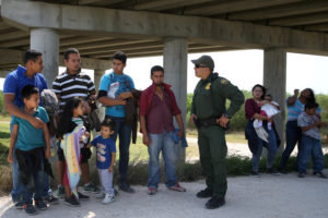 Border patrol agent Sergio Ramirez talks with immigrants who illegally crossed the border from Mexico into the U.S. in the Rio Grande Valley sector, near McAllen, Texas, in April. Photo by Loren Elliott/Reuters