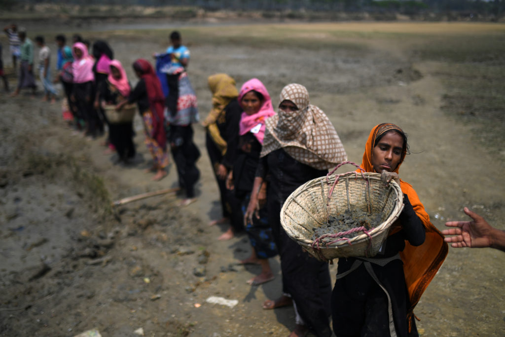 Rohingya refugee women carry baskets of dried out mud from the riverbed to help raise the ground level of the camp in preparation for monsoon season, in Shamlapur refugee camp in Cox's Bazaar, Bangladesh, March 24, 2018. Photo by Clodagh Kilcoyne/Reuters