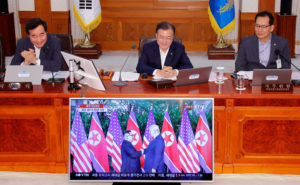 South Korean President Moon Jae-in looks at a TV broadcasting a news report on summit between the U.S. and North Korea during a cabinet meeting at the Presidential Blue House in Seoul, South Korea. Photo by Yonhap via Reuters