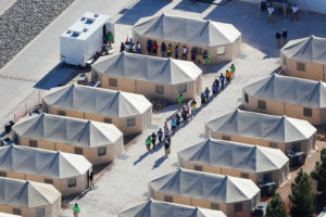 Immigrant children housed in a tent encampment, shown walking in single file at the facility near the Mexican border in Tornillo, Texas, on June 19, 2018. Photo by Mike Blake/Reuters