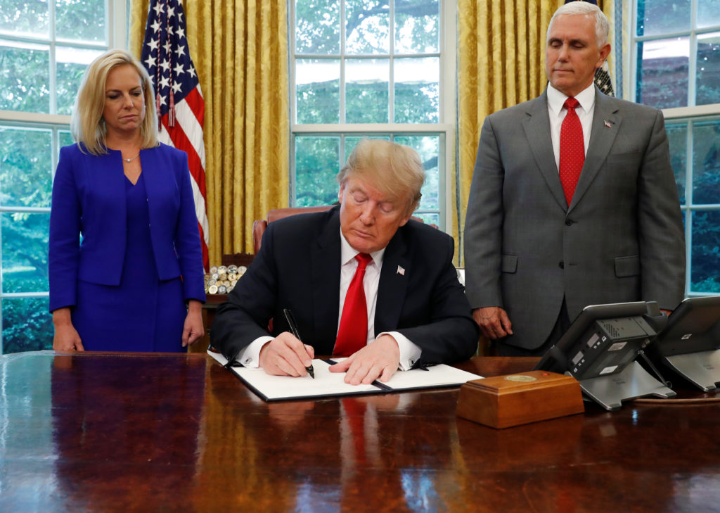 U.S. President Donald Trump signs an executive order on immigration policy with DHS Secretary Kirstjen Nielsen and Vice President Mike Pence at his sides in the Oval Office at the White House in Washington, U.S., June 20, 2018.  Leah Millis/Reuters