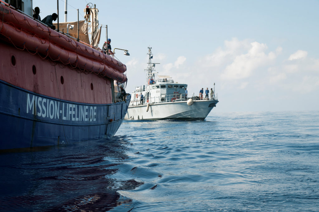A Libyan coast guard vessel is seen next to the Mission Lifeline rescue boat in the central Mediterranean Sea. Picture taken June 21, 2018. Photo by Hermine Poschmann/Misson-Lifeline via Reuters