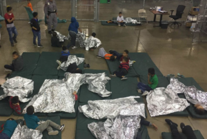 Children rest under mylar blanket at an immigrant housing facility in McAllen, Texas. Photo handout from U.S. Customs and Border Protection.