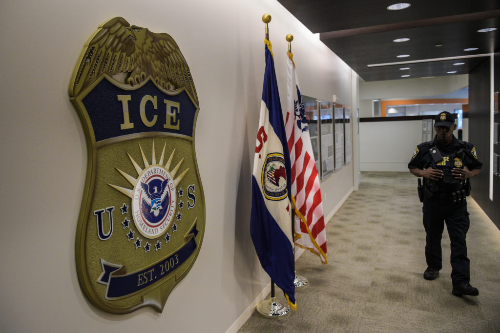 A law enforcement officer walks past ICE logo ahead of a press conference at the U.S. Immigration and Customs Enforcement headquarters in Washington, D.C. Photo by Salwan Georges/The Washington Post via Getty Images