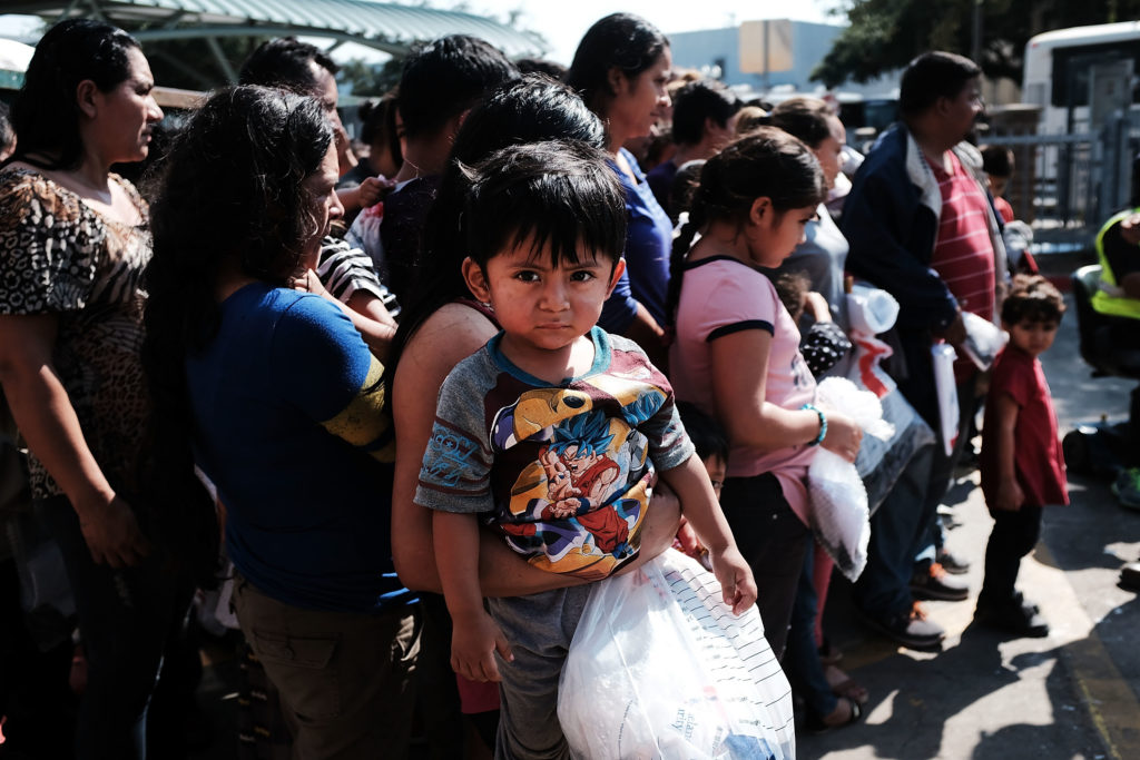 Dozens of women, men and their children, many fleeing poverty and violence in Honduras, Guatamala and El Salvador, arrive at a bus station following release from Customs and Border Protection on June 23 in McAllen, Texas. Photo by Spencer Platt/Getty Images