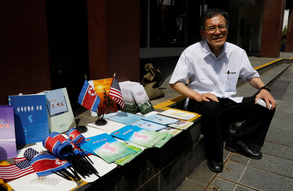 Jun Miyagawa, a Japanese speciality bookdealer on North Korea publications, sits next to North Korean publications he is displaying next to St. Regis hotel in Singapore June 11, 2018.  REUTERS/Tyrone Siu