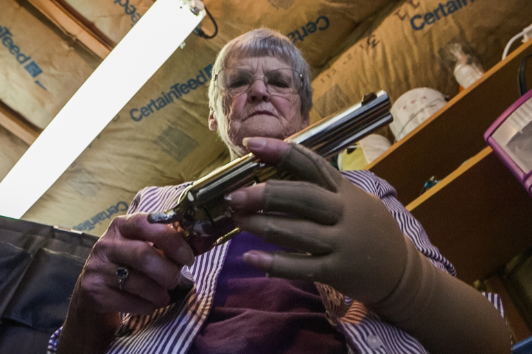 "Dee Hill examines the last of the guns that once belonged to her husband, Darrell Hill. ""I no longer have any guns in my home,"" she says. Photo by Frank Carlson/PBS NewsHour"