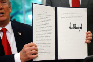 U.S. President Donald Trump displays an executive order on immigration policy after signing it in the Oval Office at the White House in Washington, U.S., June 20, 2018. REUTERS/Leah Millis