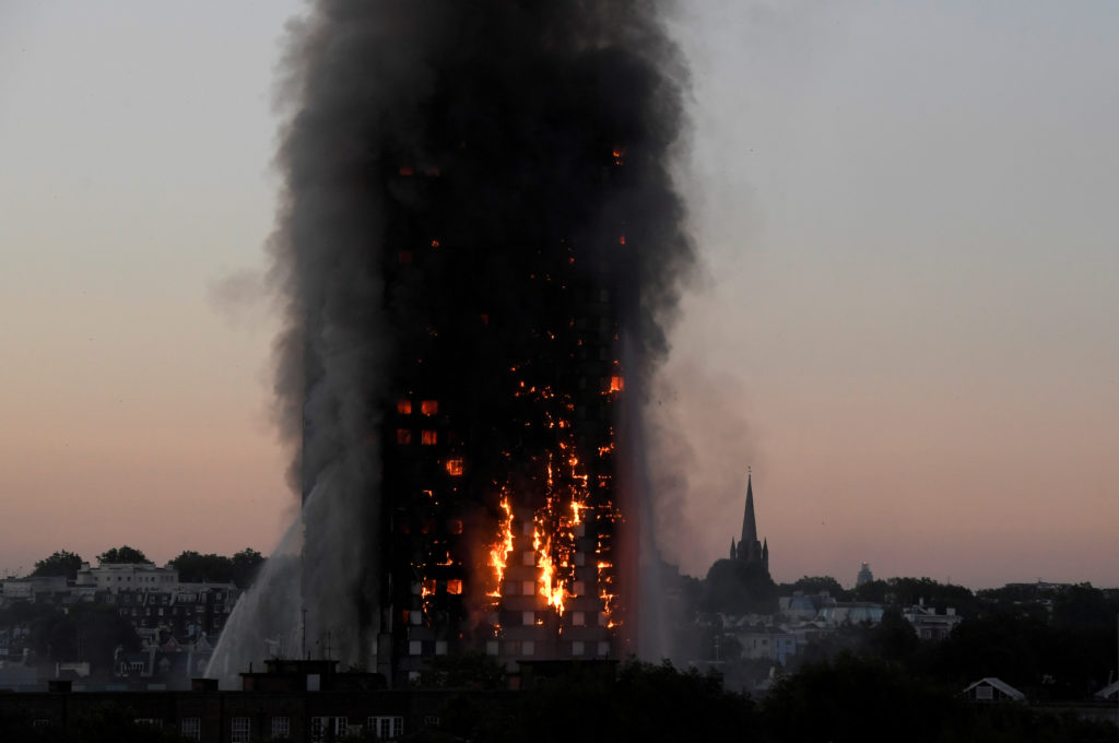 FILE PHOTO: Flames and smoke billow as firefighters deal with a serious fire in the Grenfell Tower apartment block at Latimer Road in West London, Britain June 14, 2017. British officials have opened an independent inquiry into what caused the fire, which killed 72 last year. REUTERS/Toby Melville/File Photo