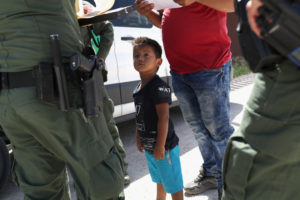 A boy and father from Honduras are taken into custody by U.S. Border Patrol agents near the U.S.-Mexico Border on June 12, 2018 near Mission, Texas. Photo by John Moore/Getty Images