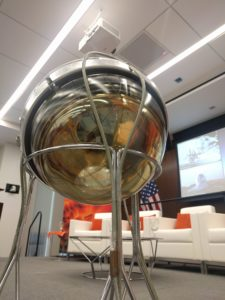 This is an optical sensor, identical to the 5,000 devices buried up to a mile under the ice at the IceCube Neutrino Observatory. Light generated in a neutrino collision event is collected by the gold-colored dish and transformed into an electrical signal. Photo by Amanda Grennell