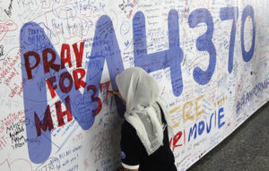 A woman writes on a banner of well wishes for the passengers of the missing Malaysia Airlines Flight MH370 at Kuala Lumpur International Airport, in March 2014. Photo by Edgar Su/Reuters