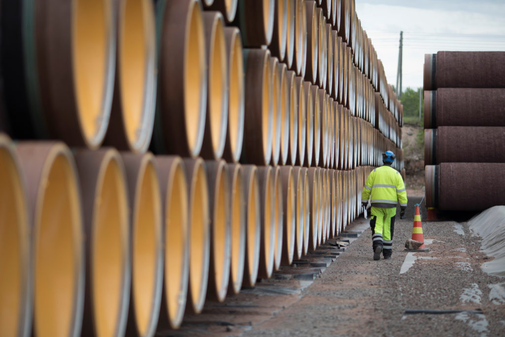 A man walks by a stack of North Stream 2 pipes in Kotka, Finland on June 8, 2017. Photo by Axel Schmidt/Reuters