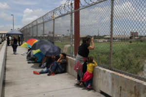 A Honduran mother and her 3-year-old daughter wait with fellow asylum seekers on the Mexican side of the Brownsville-Matamoros International Bridge after being denied entry by U.S. Customs and Border Protection officers near Brownsville, Texas, U.S., June 24, 2018. REUTERS/Loren Elliott - RC1653417760