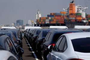 Cars are lined up past a container vessel at the port in Valencia, Spain. Photo by Heino Kalis/Reuters