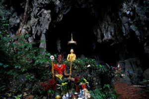 A spirit and Buddha statues are seen in front of a cave near the Tham Luang cave complex in the northern province of Chiang Rai, Thailand. Photo by Soe Zeya Tun/Reuters