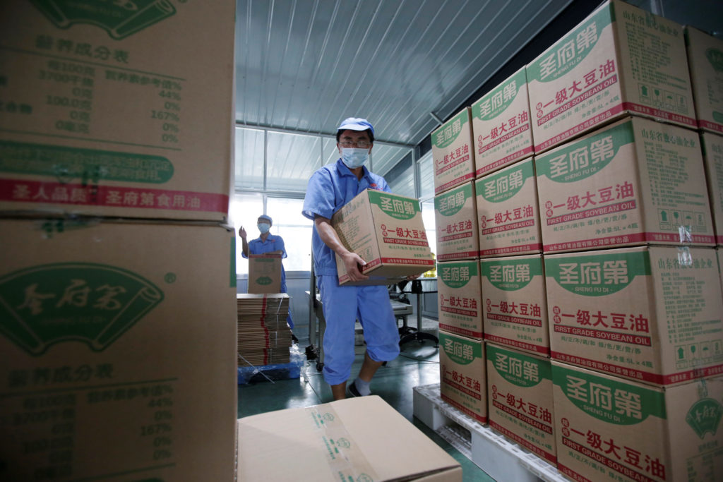 A worker carries boxes of bottled soybean oil made from the U.S. imported soybeans at the plant of Liangyou Industry and Trade Co., Ltd in Qufu, Shandong province, China. Photo by Jason Lee/Reuters