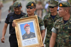 An honor guard hold up a picture of Samarn Kunan, 38, a former member of Thailand's elite navy SEAL unit who died working to save 12 boys and their soccer coach trapped inside a flooded cave, at an airport in Rayong province, Thailand. Photo by Panumas Sanguanwong/Reuters