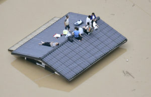 An aerial view shows local residents seen on the roof of submerged house at a flooded area as they wait for a rescue in Kurashiki, southern Japan, in this photo taken by Kyodo. Photo by Kyodo via Reuters